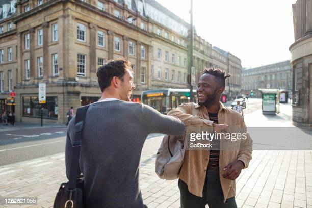 say hello with an elbow bump - downtown stock pictures, royalty-free photos & images
