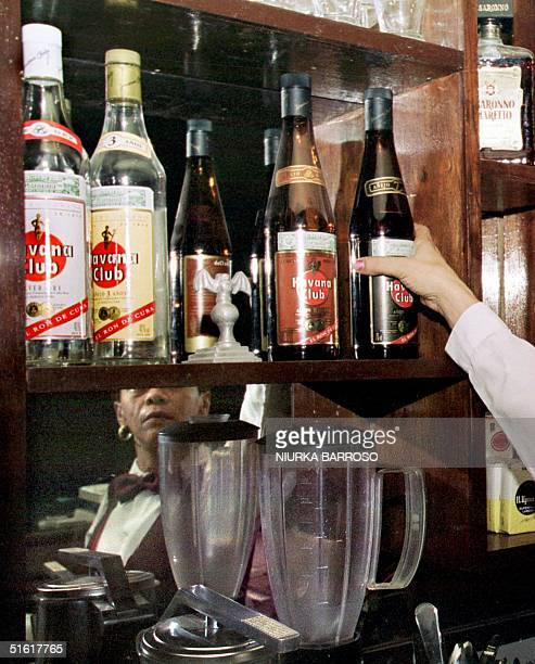 Sayli Cisnero grabs a bottle of Havana Club to prepare a cocktail in the bar of the Bacardi building 26 August in Havana AFP PHOTO/NIURKA BARROSO