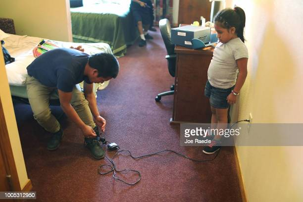 Saylin watches as her father Nery plugs in his ankle monitor for charging as they are cared for in an Annunciation House facility after they were...