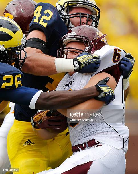 Saylor Lavallii of the Central Michigan Chippewas is tackled by Ben Gedeon of the Michigan Wolverines during a first quarter kick return at Michigan...