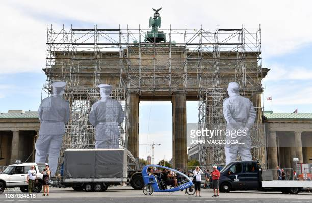 A scaffold is put up in front of Berlin's landmark the Brandenburg Gate on September 21 as French artist JR installs an art work based on historic...