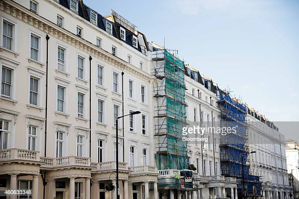 Scaffolding covers the facades of white stucco terraced properties undergoing renovation in the Belgravia district of London UK on Tuesday Dec 16...