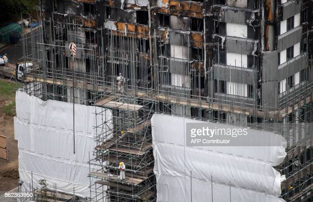 Scaffolding is seen with coverings at the base of the burnedoutshell of Grenfell Tower in London on October 17 2017 as investigations continue into...