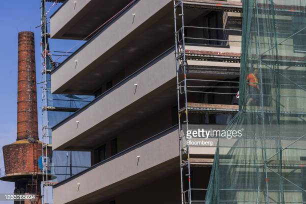 Scaffolding on a residential apartment construction site beside an inactive industrial chimney at a building site, on a plot of brownfield land in...