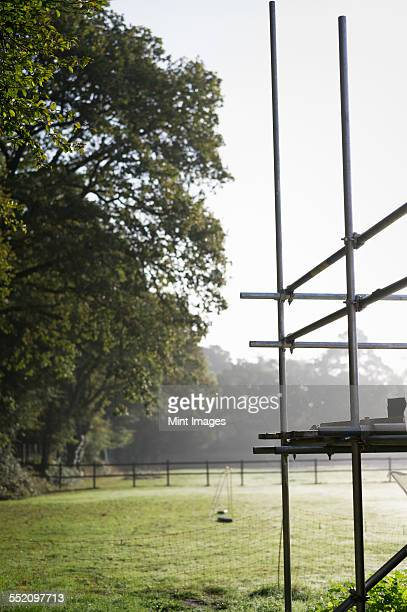 Scaffolding on the corner of a building. A small football goal net in a garden.