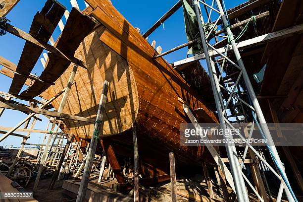 Scaffolding supports the hull during handmade construction of an ancient timber dhow in a ship building yard Sur Ash Sharqiyah Region Gulf of Oman...