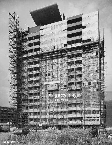 Scaffolding surrounds a new development of London County Council flats under construction by construction firm Wimpey on the Barbican Estate in the...