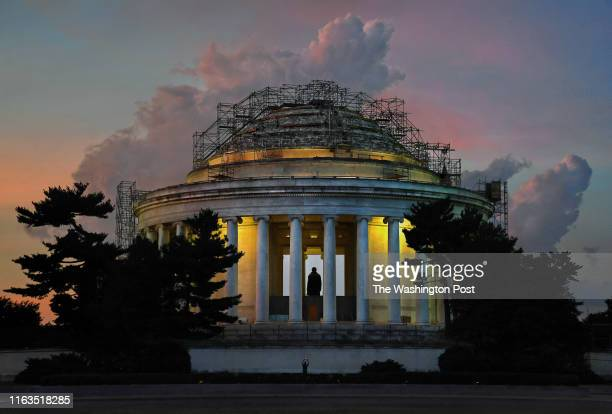 Scaffolding surrounds the Jefferson Memorial as it is undergoing a roof makeover and repair in Washington DC on August 17 2019 A tourist standing...