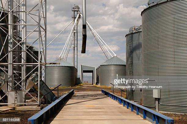 a scale for weighing grain is surrounded by grain storage silos - timothy hearsum stock pictures, royalty-free photos & images