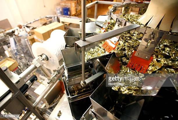 A scale weighs and separates wrapped candy for packaging on the production line at the See's Candies Inc lollipop factory in Burlingame California US...
