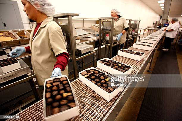 Scalers weigh boxes of assorted chocolates on the production line at the See's Candies Inc. Packing facility in South San Francisco, California,...