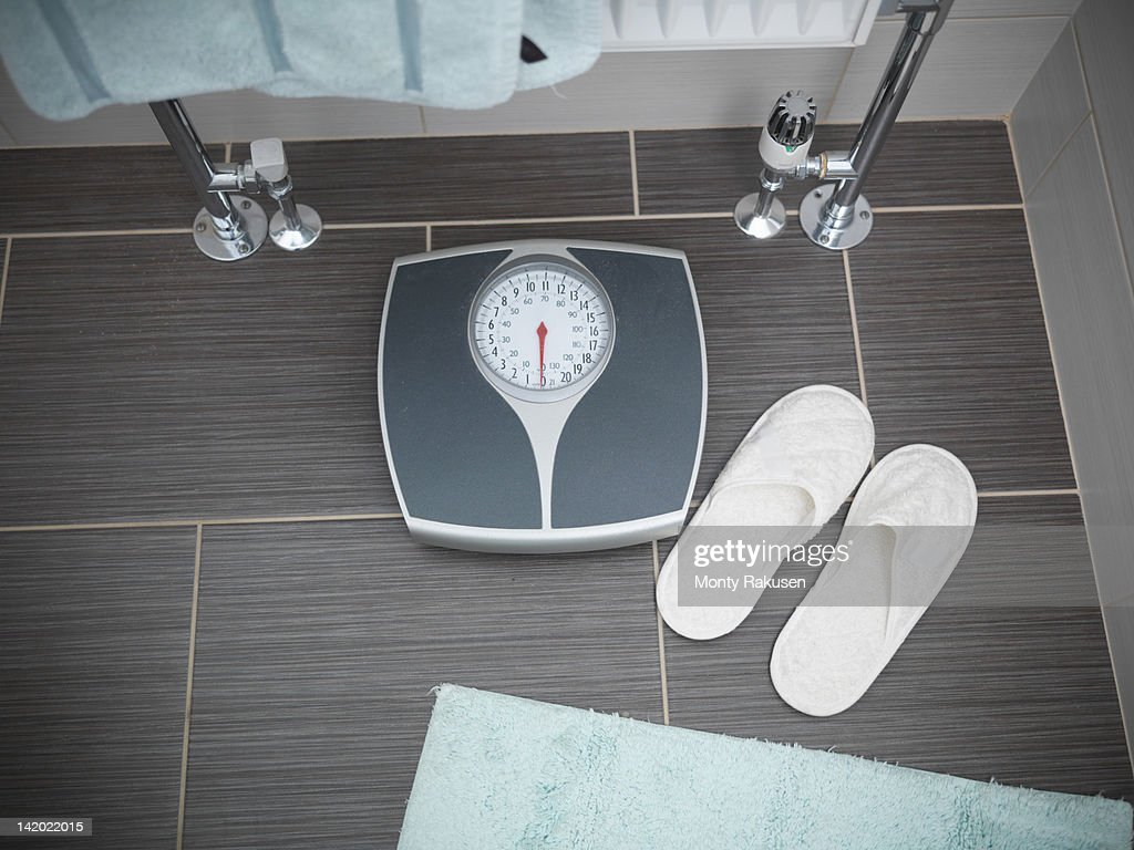 Scales and slippers in senior person's bathroom : ストックフォト