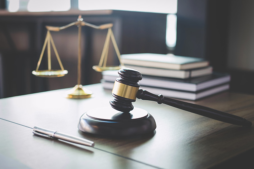 Scales of justice and Gavel on wooden table and Lawyer or Judge working with agreement in Courtroom, Justice and Law concept 939262058