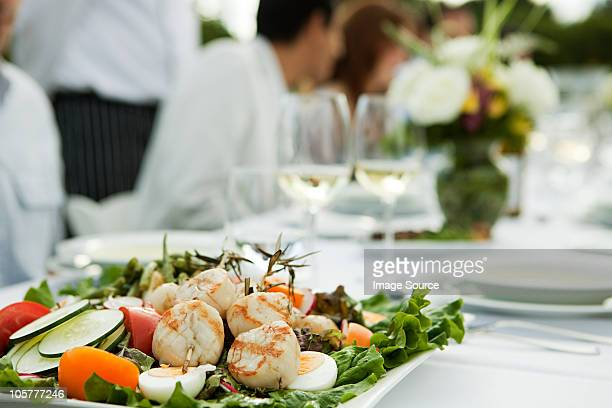 Scallop and salad dish at dinner party