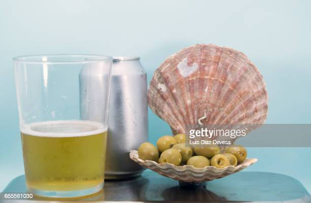scallop shell filled with green olives and beer drink can - luques olive stock pictures, royalty-free photos & images