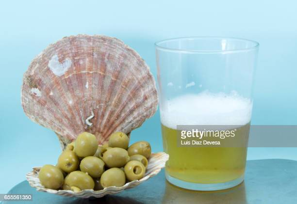 scallop shell filled with green olives and pint of beer - luques olive stock pictures, royalty-free photos & images