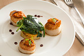 plated scallops with red pepper sauce