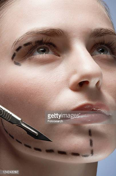 Scalpel near woman's face with dotted lines, close-up