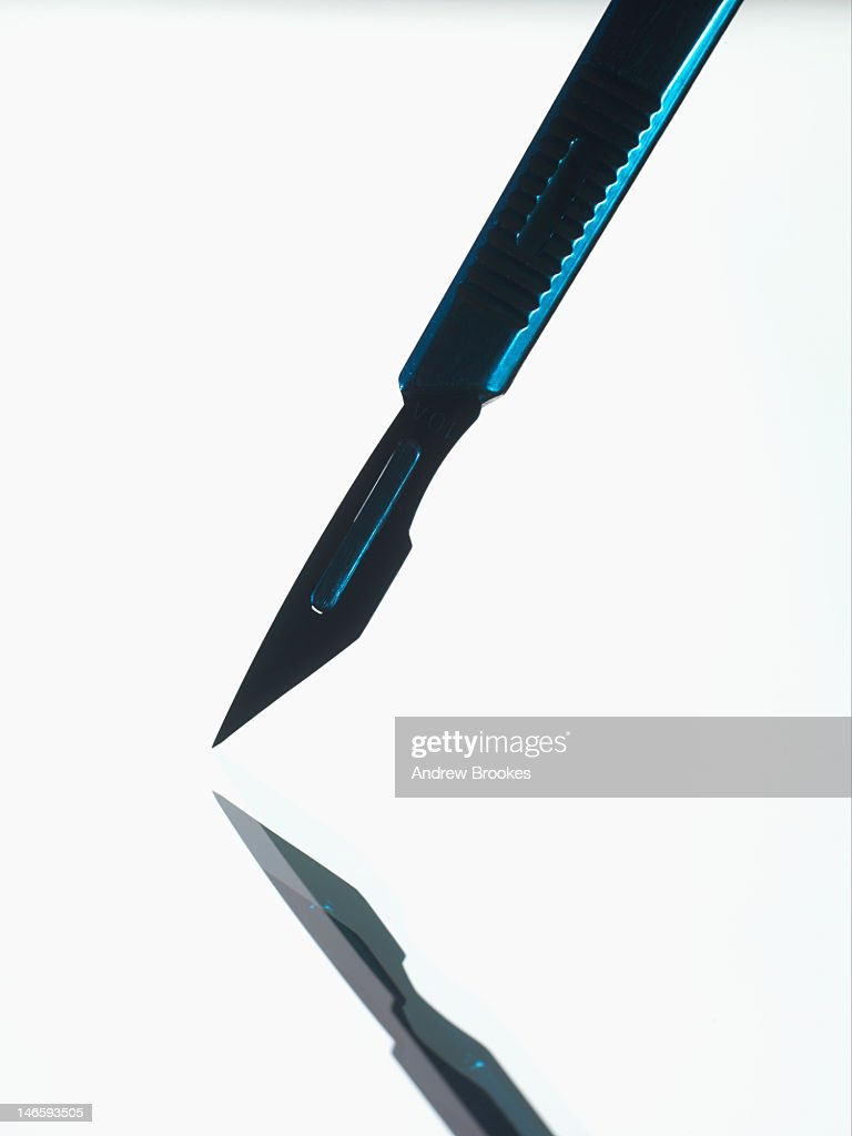 Scalpel on reflective surface : Stock Photo