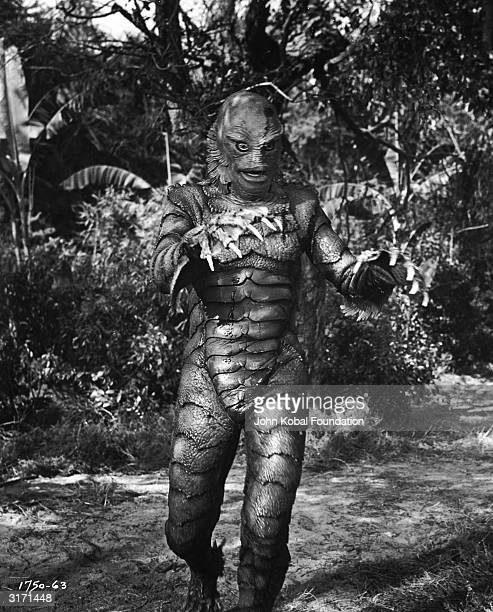 A scaly creature with webbed and clawed hands walks along a forest path in the film 'Creature from the Black Lagoon' directed by Jack Arnold for...