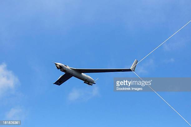 a scan eagle unmanned aerial vehicle makes an arrested recovery on the skyhook recovery system. - military drones stock photos and pictures