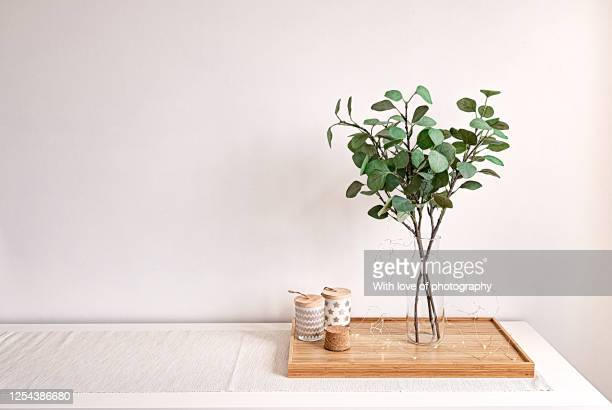 scandi white interior decoration green leaves in a vase and candles on wood, white interior background stillife - eucalyptus tree stock pictures, royalty-free photos & images
