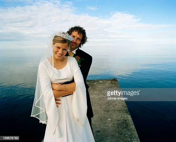 Scandinavia, Sweden, Oland, Groom and bride embracing on jetty, smiling, portrait