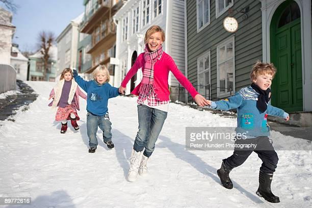 Scandinavian children running in snow