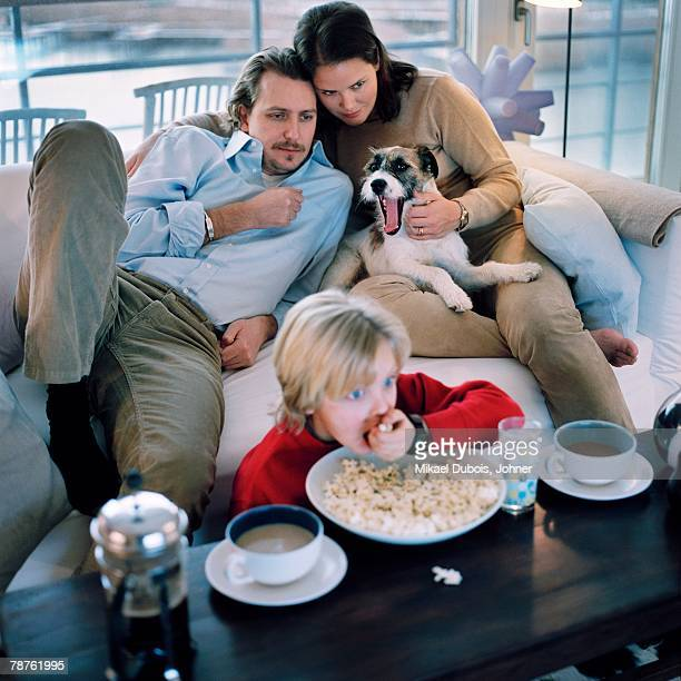 Scandinavian family sitting in a sofa watching TV Hammarby sjastad Sweden.
