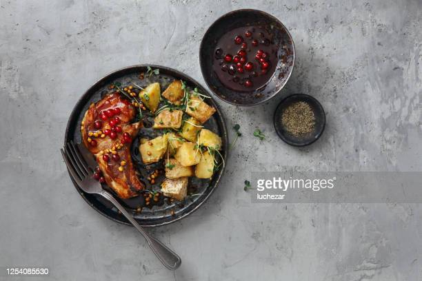 scandinavian food. pork chops with wild lingonberry sauce and baked potato wedges with herbs - pork stock pictures, royalty-free photos & images