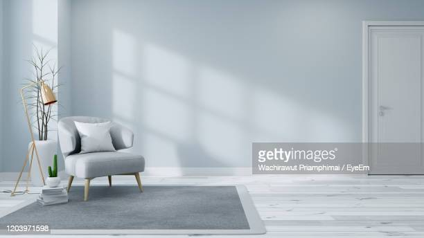 scandinavian interior of living room concept, light gray sofa with gold lamp on white flooring - indoors stock-fotos und bilder