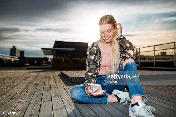 scandinavian looking generation-z blonde woman on rooftop in summer - military style stock pictures, royalty-free photos & images