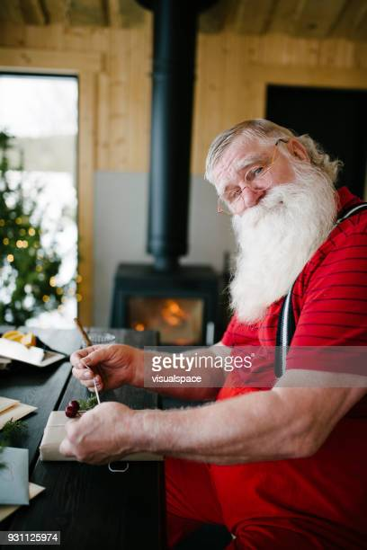 Scandinavian Santa Claus wrapping presents in his living room