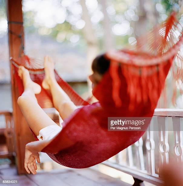 A Scandinavian woman laying in a red hammock.