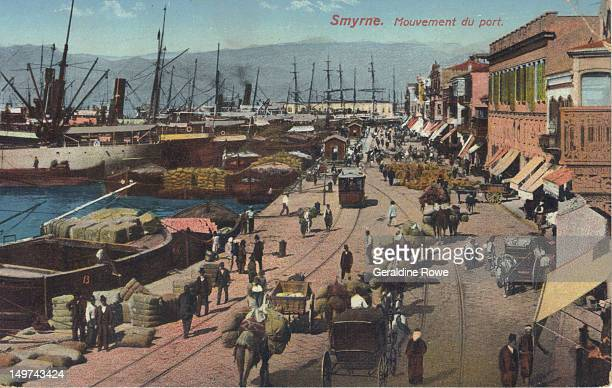 Scanned image of a hand coloured postcard dated around 1910 of people and carts by Smyrna Port in Turkey Boats a tram mountains and buildings with...