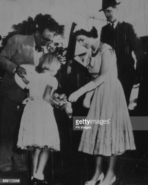 **Scanned lowres from contact** The Queen accepting a bouquet from Vivien Irving representing the European children of Fiji Watching the presentation...