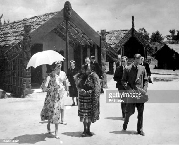 **Scanned lowres from contact** The Queen sheltering beneath a sunshade talks with Maori guide Rangi as she leaves the Meeting House during the visit...