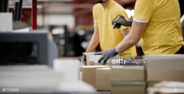 scanning boxes in warehouse - beige glove stock photos and pictures