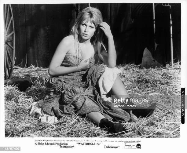 Scantily clad Margaret Blye sitting in hay in a scene from the stage play 'Waterhole' 1967