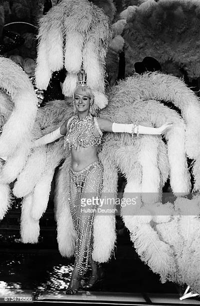 A scantily clad showgirl on stage during the Paris theater's spectacular centenary performance