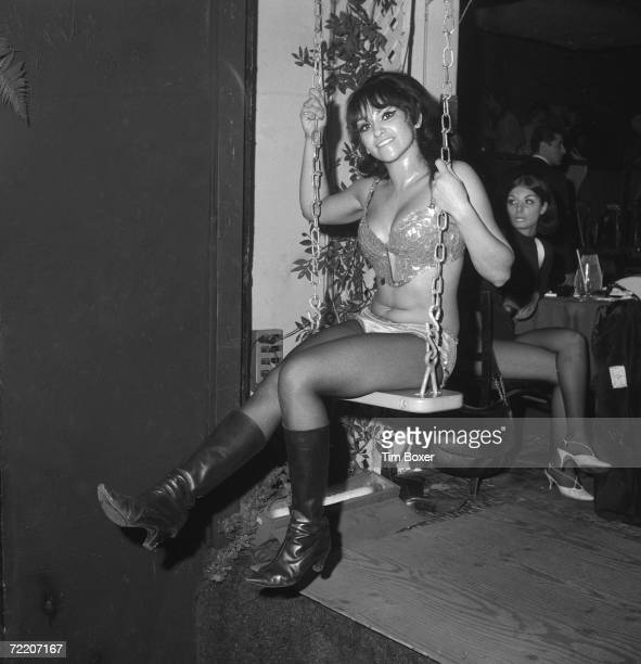 A scantilyclad gogo dancer swings on a swing at a discotheque 1968