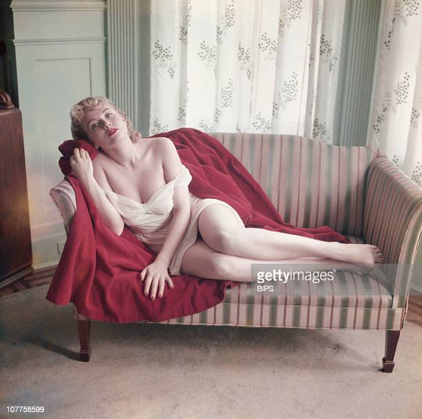 A scantilyclad young woman poses on a sofa circa 1955
