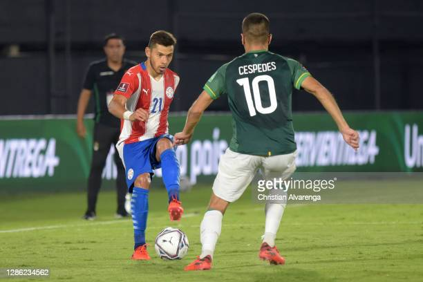 Óscar Romero of Paraguay competes for the ball with Boris Cespedes of Bolivia during a match between Paraguay and Bolivia as part of South American...