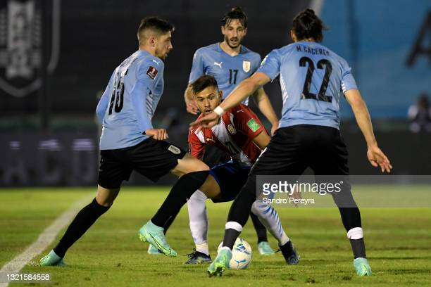 Óscar Romero of Paraguay fights for the ball with Federico Valverde and Martín Cáceres of Uruguay during a match between Uruguay and Paraguay as part...