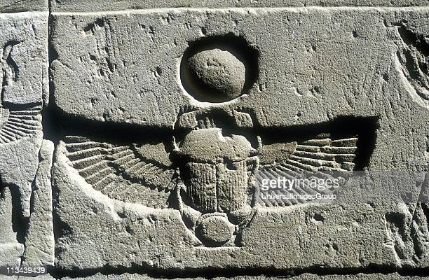 Scarab beetle and vulture wings under disk of the sun Limestone relief Edfu