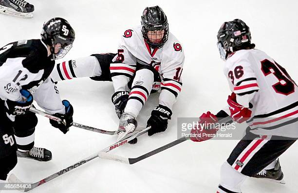 Scarborough's Cameron Smith gets the puck stuck under his skate during first period action as Dillon Pratt of St Dom's and Scarborough's John...