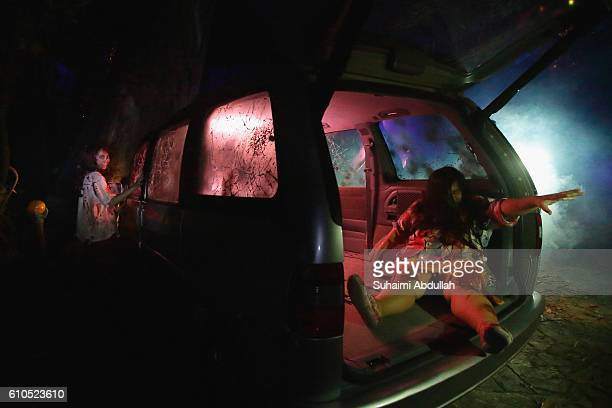 Scare actresses perform in the Suicide Forest scare zone during the Halloween Horror Nights 6 media preview at Universal Studios Singapore on...