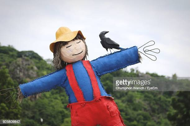 scarecrow by mountain against sky - scarecrow agricultural equipment stock photos and pictures