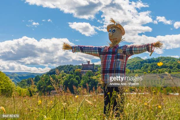 scarecrow on grassy field against sky during sunny day - scarecrow agricultural equipment stock photos and pictures