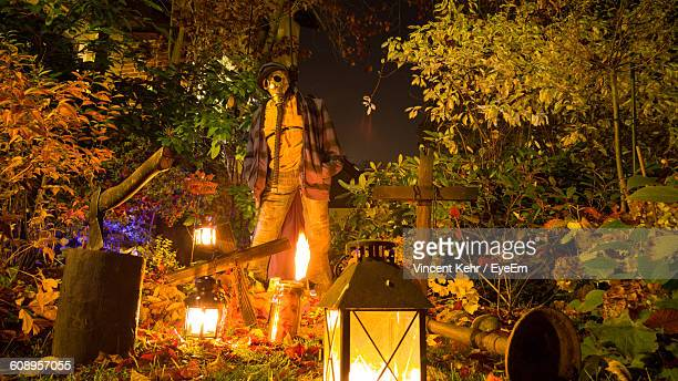 Scarecrow With Gas Mask Amidst Trees And Illuminated Lanterns At Night